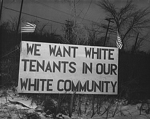 "Image showing a large white sign at the entrance to a housing development reading ""WE WANT WHITE TENANTS IN OUR WHITE COMMUNITY"" in capital letters. Two small American flags fly at the top corners of the sign."