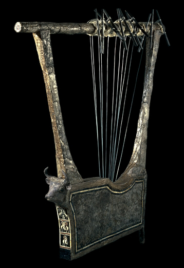"Silver lyre from Ur, southern Iraq, c. 2600-2400 B.C.E., 106 x 97 cm  This lyre was found in the ""Great Death-Pit,"" one of the graves in the Royal Cemetery at Ur accompanied by seventy-four bodies—six men and sixty-eight women—laid down in rows on the floor of the pit. Three lyres were piled one on top of another. They were all made from wood which had decayed by the time they were excavated, but two of them, of which this is one, were entirely covered in sheet silver attached by small silver nails. The plaques down the front of the sounding box are made of shell. The silver cow's head decorating the front has inlaid eyes of shell and lapis lazuli. The edges of the sound box have a narrow border of shell and lapis lazuli inlay.  When found, the lyre lay in the soil. The metal was very brittle and the uprights were squashed flat. First it was photographed, and then covered in wax and waxed cloth to hold it together for lifting. The silver on the top and back edge of the sounding box had been destroyed. Some of the silver preserved the impression of matting on which it must have originally lain. Eleven silver tubes acted as the tuning pegs.  Such instruments were probably important parts of rituals at court and temple. There are representations of lyre players and their instruments on cylinder seals, and on the Standard of Ur being played alongside a possible singer."