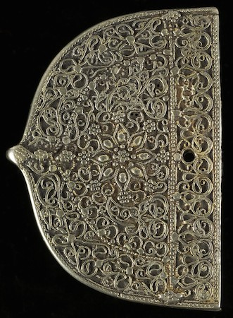 Belt Fitting (Yemen), the back is blank except for an Arabic stamp with the name and date of the Muslim ruler, Imam al-Mansur al-Husayn, and an engraved inscription in Hebrew names the silversmith, Yahya Tayyib