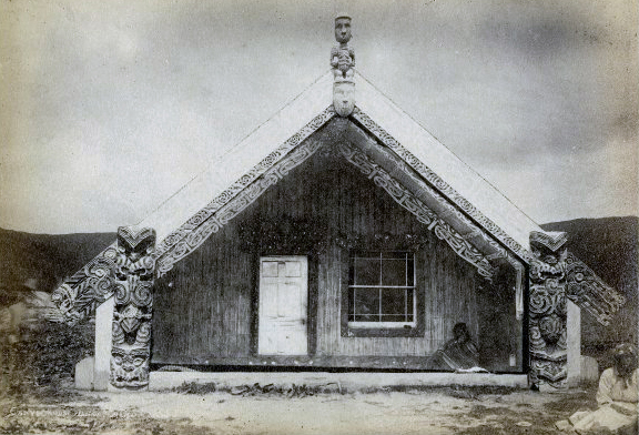 Josiah Martin, Exterior of a Maori marae (community meeting house), Hinemihi, in the village of Te Wairoa, 1881, albumen print, 15.3 x 20.5 cm © The Trustees of the British Museum. Front of the house with carved end posts on either side of the veranda, maihi (carved barge-boards), raparapa (projecting boards at the end of the maihi), tekoteko( anthropomorphic figurative carving at the front of the apex of the roof), koruru (carved mask depicting the ancestor the house is named for, placed below the tekoteko), pare (carved lintel above doorway), and carving above the window; two people sit in front of the house: a Maori man sitting on the platform in front of the house, wrapped in a stripped blanket, and a Maori woman in Western-style clothing sitting on the ground in the foreground, on the right of the image.