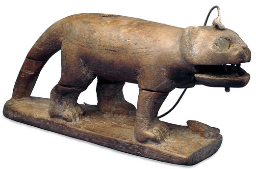 Wooden toy cat, c. 1550-1070 B.C.E., 5.3 x 11.7 x 3 cm, Thebes, © Trustees of the British Museum. Rock crystal inlays are used for the eyes, and the teeth are of bronze. The lower jaw can be moved, using a string (modern) which runs through a hole which runs through from the top of the head.