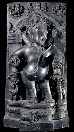 Figure of Gaṇeśa, 13th century, schist, 119 cm high, © Trustees of the British Museum. Typically corpulent and holding a bowl of sweets, the god is shown standing on a lotus pedestal at the base of which crouches his rat 'vahana'. His anklets are of snakes, as is the sacred thread wound across his chest. The arch within which he stands is of a standard Indian decorative type with a lion mask (kirttimukha) at the top, and aquatic monsters (makaras) at each end.