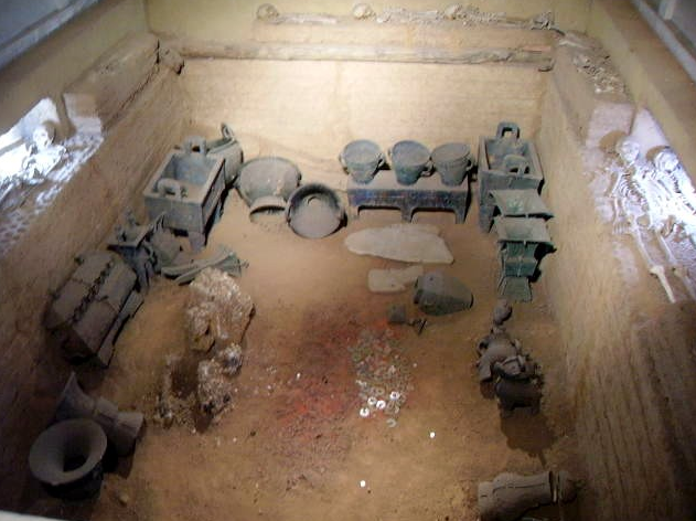 Brick-lined tomb holding skeletons on the side and dark-colored pottery in the center.