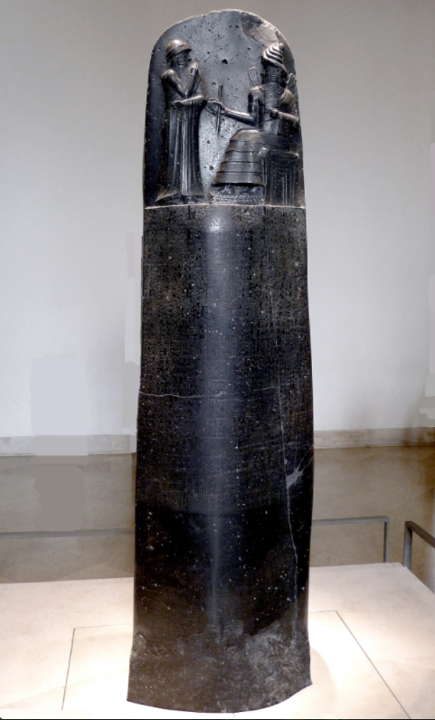 Law Code of Hammurabi inscribed on a black stone slab, rounded at the top and rectangular at the bottom. At the rounded top of the slab, taking up about a quarter of the space on the front, is a relief sculpture of two people, one sitting in a throne and wearing an elaborate gown, the other standing with their arms crossed. The lower portion of the slab has law codes written on it in cuneiform.
