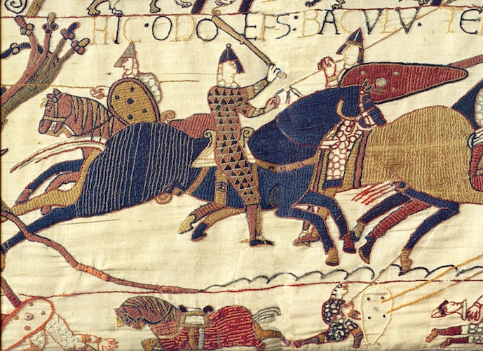 """The inscription above Odo (partially cut off in the reproduction above) reads, """"Here, Odo the Bishop, with a staff (baculum) encourages the young warriors,""""  Bayeux Tapestry, c. 1070, embroidered wool on linen, 20 inches high (Bayeux Museum)"""