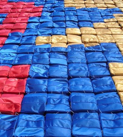 Closeup of blue, yellow, and red backpacks (detail), Ai Weiwei, Remembering, 2009, backpacks on the facade of the Haus der Kunst (Munich)